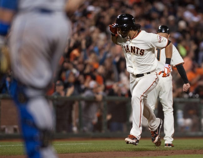 Sep 26, 2013; San Francisco, CA, USA; San Francisco Giants center fielder Angel Pagan (16) salutes his team mates in the dugout after hitting a home run during the eighth inning against the Los Angeles Dodgers at AT&T Park. The San Francisco Giants defeated the Los Angeles Dodgers 3-2. Mandatory Credit: Ed Szczepanski-USA TODAY Sports