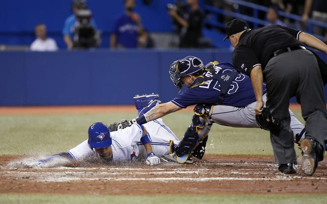Sep 27, 2013; Toronto, Ontario, CAN; Tampa Bay Rays catcher Jose Lobaton (59) tags out Toronto Blue Jays second baseman Ryan Goins (left) in the fourth inning as home plate umpire Eric Cooper (right) watches at Rogers Centre. Mandatory Credit: John E. Sokolowski-USA TODAY Sports