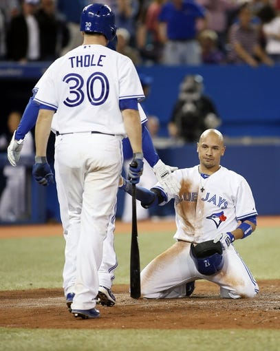 Sep 27, 2013; Toronto, Ontario, CAN; Toronto Blue Jays second baseman Ryan Goins (right) reacts after being tagged out at home plate by Tampa Bay Rays catcher Jose Lobaton (not pictured) in the fourth inning at Rogers Centre. Mandatory Credit: John E. Sokolowski-USA TODAY Sports