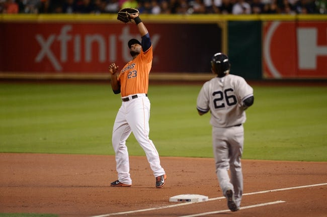 Sep 27, 2013; Houston, TX, USA; Houston Astros first baseman Chris Carter (23) catches a pop fly by New York Yankees shortstop Eduardo Nunez (26) during the first inning at Minute Maid Park. Mandatory Credit: Thomas Campbell-USA TODAY Sports