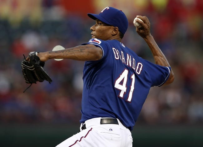 Sep 27, 2013; Arlington, TX, USA; Texas Rangers starting pitcher Alexi Ogando (41) delivers a pitch to the Los Angeles Angels during the first inning of a baseball game at Rangers Ballpark in Arlington. Mandatory Credit: Jim Cowsert-USA TODAY Sports
