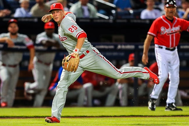 Sep 27, 2013; Atlanta, GA, USA; Philadelphia Phillies third baseman Cody Asche (25) attempts to throw to first after fielding a ground ball in the second inning against the Atlanta Braves at Turner Field. Mandatory Credit: Daniel Shirey-USA TODAY Sports