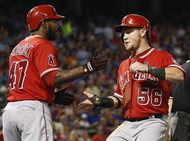 Sep 27, 2013; Arlington, TX, USA; Los Angeles Angels right fielder Kole Calhoun (56) is congratulated by second baseman Howie Kendrick (47) after scoring against the Texas Rangers during the fifth inning at Rangers. Mandatory Credit: Jim Cowsert-USA TODAY Sports