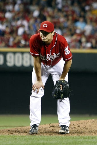 Sep 27, 2013; Cincinnati, OH, USA; Cincinnati Reds starting pitcher Homer Bailey watches from the mound after giving up a two-run home run to Pittsburgh Pirates third baseman Pedro Alvarez (not pictured) in the sixth inning at Great American Ball Park. Pittsburgh won 4-1. Mandatory Credit: David Kohl-USA TODAY Sports