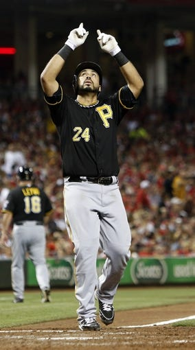 Sep 27, 2013; Cincinnati, OH, USA; Pittsburgh Pirates third baseman Pedro Alvarez points to the sky at home plate after hitting a two-run home run off Cincinnati Reds starting pitcher Homer Bailey (not pictured) in the sixth inning at Great American Ball Park. Pittsburgh won 4-1. Mandatory Credit: David Kohl-USA TODAY Sports