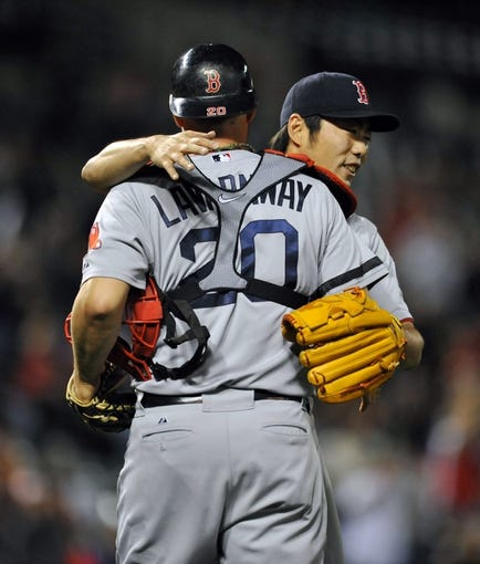 Sep 27, 2013; Baltimore, MD, USA; Boston Red Sox catcher Ryan Lavarnway (20) congratulates pitcher Koji Uehara (19) after a game against the Baltimore Orioles at Oriole Park at Camden Yards. The Red Sox defeated the Orioles 12-3. Mandatory Credit: Joy R. Absalon-USA TODAY Sports
