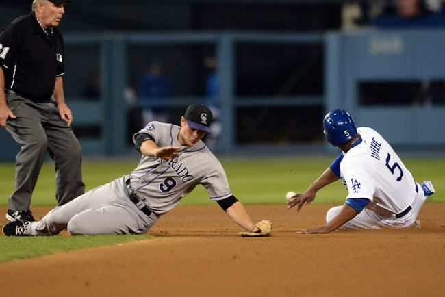 Sep 27, 2013; Los Angeles, CA, USA; Colorado Rockies second baseman DJ LeMahieu (9) reaches for the throw as Los Angeles Dodgers third baseman Juan Uribe (5) steals second base in the third inning at Dodger Stadium. Mandatory Credit: Jayne Kamin-Oncea-USA TODAY Sports