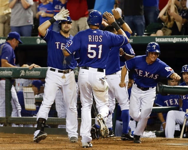Sep 27, 2013; Arlington, TX, USA; Texas Rangers right fielder Alex Rios (51) is congratulated by first baseman Mitch Moreland (left) after scoring against the Los Angeles Angels during the seventh inning of a baseball game at Rangers Ballpark in Arlington. The Rangers won 5-3. Mandatory Credit: Jim Cowsert-USA TODAY Sports