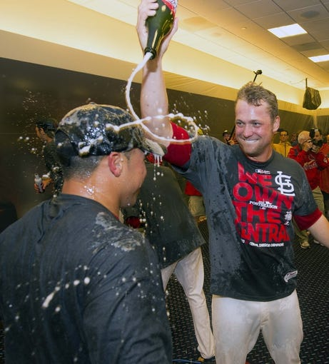 Sep 27, 2013; St. Louis, MO, USA; St. Louis Cardinals relief pitcher Trevor Rosenthal (26) sprays Cardinals second baseman Kolten Wong (16) with champagne after the game against the Chicago Cubs at Busch Stadium. The Cardinals defeated the Cubs 7-0 to win the National League Central Title. Mandatory Credit: Scott Rovak-USA TODAY Sports