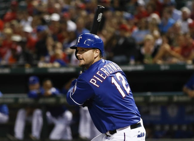 Sep 27, 2013; Arlington, TX, USA; Texas Rangers catcher A.J. Pierzynski (12) follows through for a single scoring right fielder Alex Rios (not pictured) against the Los Angeles Angels during the seventh inning of a baseball game at Rangers Ballpark in Arlington. The Rangers won 5-3. Mandatory Credit: Jim Cowsert-USA TODAY Sports