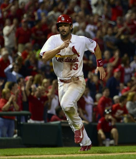 Sep 27, 2013; St. Louis, MO, USA; St. Louis Cardinals second baseman Matt Carpenter (13) scores a run on a throwing error by Chicago Cubs catcher Dioner Navarro (not pictured) at Busch Stadium. The Cardinals defeated the Cubs 7-0 to win the National League Central Title. Mandatory Credit: Scott Rovak-USA TODAY Sports