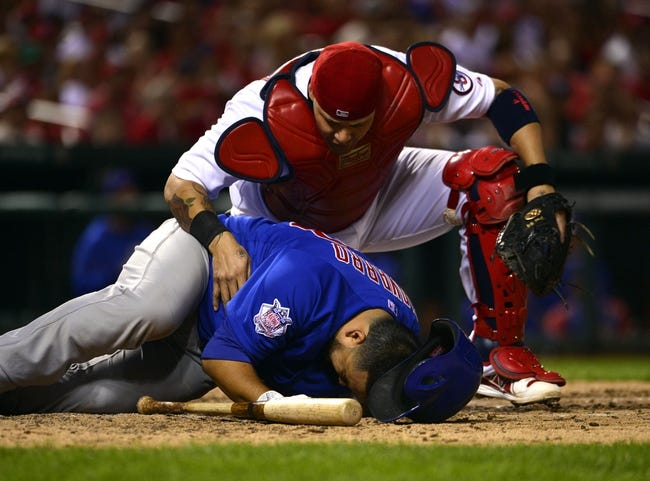 Sep 27, 2013; St. Louis, MO, USA; St. Louis Cardinals catcher Yadier Molina (4) checks on Chicago Cubs catcher Dioner Navarro (30) after being hit by a pitch at Busch Stadium. The Cardinals defeated the Cubs 7-0 to win the National League Central Title. Mandatory Credit: Scott Rovak-USA TODAY Sports