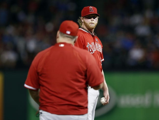 Sep 27, 2013; Arlington, TX, USA; Los Angeles Angels manager Mike Scioscia (left) heads to the mound to relieve  relief pitcher Buddy Boshers (54) of his pitching duties against the Texas Rangers during the seventh inning at Rangers Ballpark in Arlington. The Rangers won 5-3. Mandatory Credit: Jim Cowsert-USA TODAY Sports