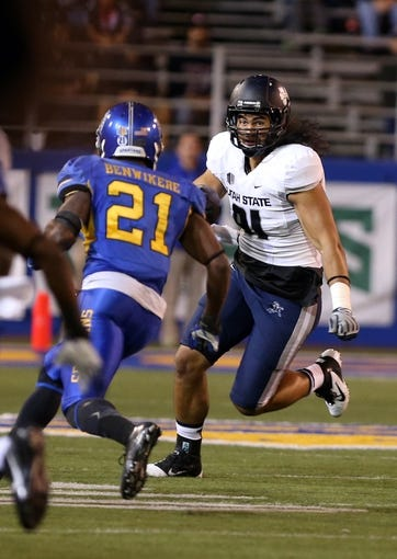 Sep 27, 2013; San Jose, CA, USA; Utah State Aggies tight end D.J. Tialavea (91) carries the ball against San Jose State Spartans cornerback Bene Benwikere (21) during the third quarter at Spartan Stadium. The Utah State Aggies defeated the San Jose State Spartans 40-12. Mandatory Credit: Kelley L Cox-USA Today Sports