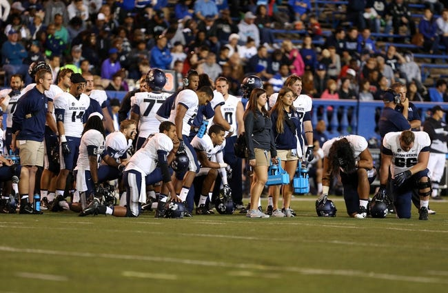 Sep 27, 2013; San Jose, CA, USA; Utah State Aggies players take a knee for a San Jose State Spartans injury during the third quarter at Spartan Stadium. The Utah State Aggies defeated the San Jose State Spartans 40-12. Mandatory Credit: Kelley L Cox-USA TODAY Sports