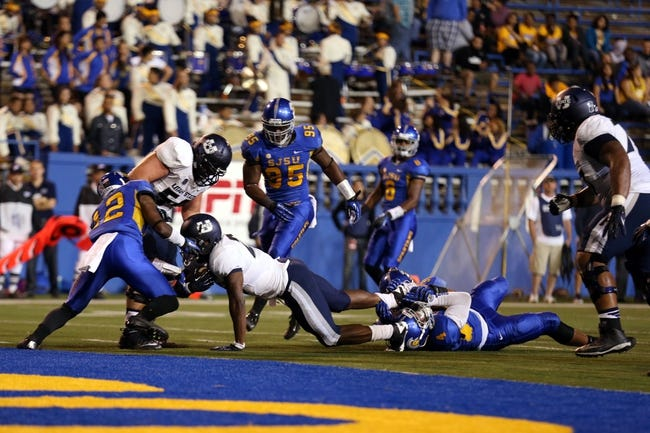 Sep 27, 2013; San Jose, CA, USA; San Jose State Spartans linebacker Christian Tago (4) holds on to the ankle of Utah State Aggies running back Robert Marshall (27) to hold him short of the end zone during the fourth quarter at Spartan Stadium. The Utah State Aggies defeated the San Jose State Spartans 40-12. Mandatory Credit: Kelley L Cox-USA TODAY Sports