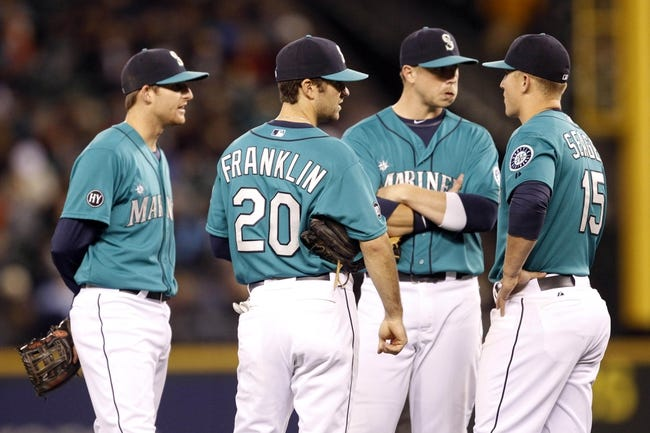 Sep 27, 2013; Seattle, WA, USA; Seattle Mariners second baseman Brad Miller (6, left), shortstop Nick Franklin (20), first baseman Justin Smoak (17) and third baseman Kyle Seager (15) talk during an eighth inning pitching change against the Oakland Athletics at Safeco Field. Mandatory Credit: Joe Nicholson-USA TODAY Sports