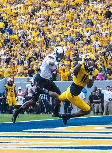Sep 28, 2013; Morgantown, WV, USA; West Virginia Mountaineers wide receiver Kevin White (11) catches a touchdown pass against Oklahoma State Cowboys cornerback Justin Gilbert (4) during the first half at Milan Puskar Stadium. Mandatory Credit: Peter Casey-USA TODAY Sports