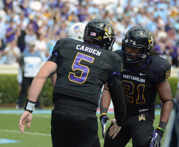 Sep 28, 2013; Chapel Hill, NC, USA; East Carolina Pirates quarterback Shane Carden (5) is congratulated by teammate Vintavious Cooper (21) after scoring a first half touchdown against the North Carolina Tarheels at Kenan Memorial Stadium. Mandatory Credit: Rob Kinnan-USA TODAY Sports