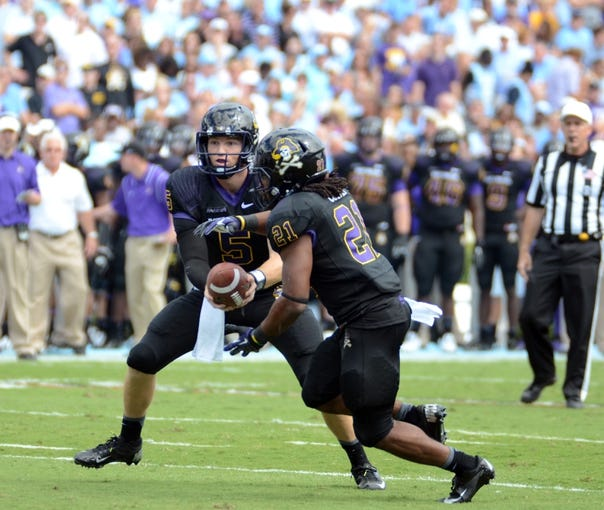 Sep 28, 2013; Chapel Hill, NC, USA; East Carolina Pirates quarterback Shane Carden (5) hands off to running back Vintavious Cooper (21) during the first half against the North Carolina Tarheels at Kenan Memorial Stadium. Mandatory Credit: Rob Kinnan-USA TODAY Sports
