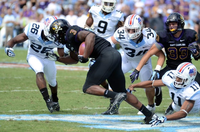 Sep 28, 2013; Chapel Hill, NC, USA; East Carolina Pirates receiver Lance Ray (3) returns a kick as North Carolina Tarheels Dominique Green (26) Jeff Schoettmer (34) and Malik Simmons (11) attempt to make a tackle during the first half at Kenan Memorial Stadium. Mandatory Credit: Rob Kinnan-USA TODAY Sports