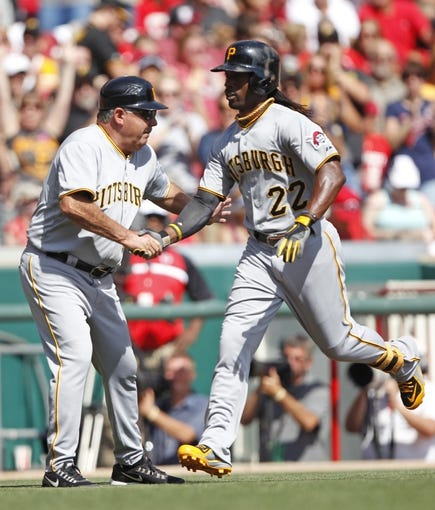 Sep 28, 2013; Cincinnati, OH, USA; Pittsburgh Pirates center fielder Andrew McCutchen (22) is congratulated by third base coach Nick Leyva (16) after hitting a home run during the third inning against the Cincinnati Reds at Great American Ball Park. Mandatory Credit: Frank Victores-USA TODAY Sports