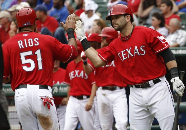 Sep 28, 2013; Arlington, TX, USA; Texas Rangers right fielder Alex Rios (51) is congratulated by first baseman Mitch Moreland (right) after scoring a run against the Los Angeles Angels during the fifth inning of a baseball game at Rangers Ballpark in Arlington. Mandatory Credit: Jim Cowsert-USA TODAY Sports