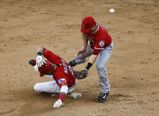 Sep 28, 2013; Arlington, TX, USA; Texas Rangers center fielder Leonys Martin (2) steals second as Los Angeles Angels second baseman Tommy Field (12) is unable to field the ball during the eighth inning of a baseball game at Rangers Ballpark in Arlington. Mandatory Credit: Jim Cowsert-USA TODAY Sports