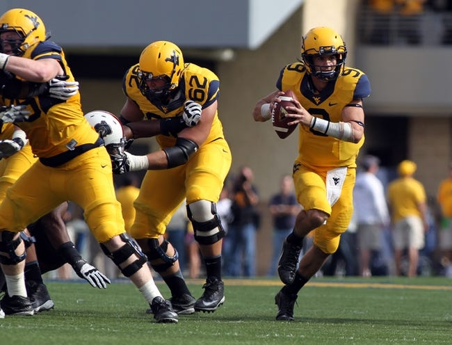 Sep 28, 2013; Morgantown, WV, USA; West Virginia Mountaineers quarterback Clint Trickett (9) runs with the ball during the second half against the Oklahoma State Cowboys at Milan Puskar Stadium. Mandatory Credit: Peter Casey-USA TODAY Sports