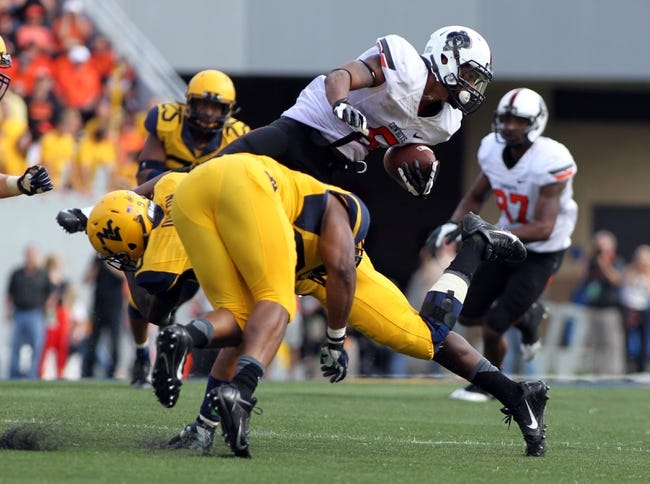 Sep 28, 2013; Morgantown, WV, USA; Oklahoma State Cowboys wide receiver Josh Stewart (5) is tackled by West Virginia Mountaineers safety K.J. Dillon (9) during the fourth quarter at Milan Puskar Stadium. Mandatory Credit: Peter Casey-USA TODAY Sports