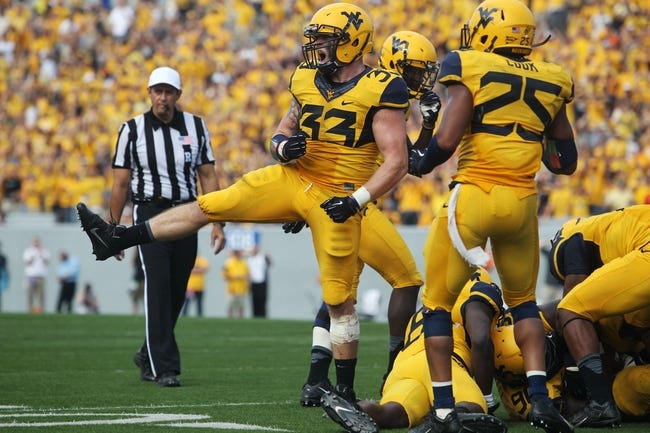 Sep 28, 2013; Morgantown, WV, USA; West Virginia Mountaineers linebacker Jared Barber (33) celebrates after making a defensive stop against the Oklahoma State Cowboys at Milan Puskar Stadium. Mandatory Credit: Peter Casey-USA TODAY Sports