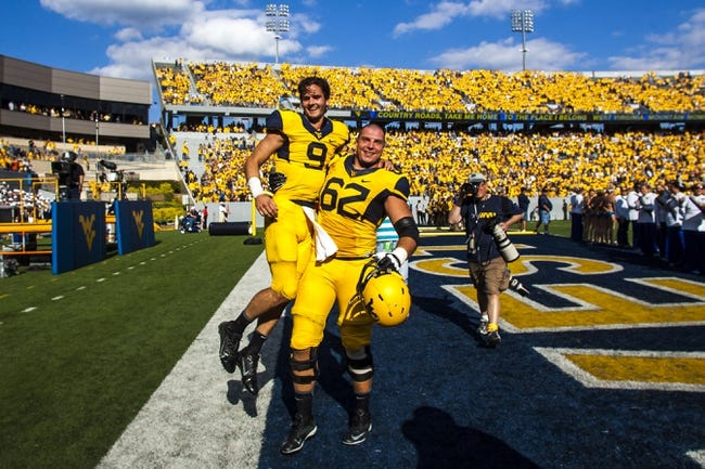 Sep 28, 2013; Morgantown, WV, USA; West Virginia Mountaineers quarterback Clint Trickett (9) and offensive linesman Curtis Feigt (62) celebrate after beating the Oklahoma State Cowboys at Milan Puskar Stadium. Mandatory Credit: Peter Casey-USA TODAY Sports