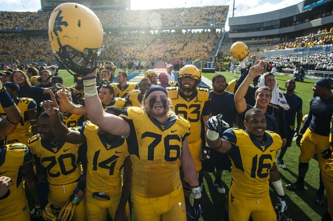 Sep 28, 2013; Morgantown, WV, USA; West Virginia Mountaineers offensive linesman Pat Eger (76) and West Virginia Mountaineers cornerback Terrell Chestnut (16) celebrate after beating the Oklahoma State Cowboys at Milan Puskar Stadium. Mandatory Credit: Peter Casey-USA TODAY Sports
