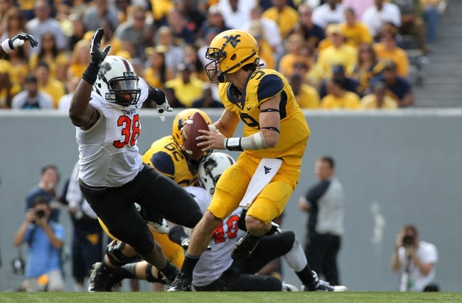 Sep 28, 2013; Morgantown, WV, USA; West Virginia Mountaineers quarterback Clint Trickett (9) avoids the pressure of Oklahoma State Cowboys defensive end Emmanuel Ogbah (38) during the second half at Milan Puskar Stadium. Mandatory Credit: Peter Casey-USA TODAY Sports