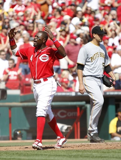 Sep 28, 2013; Cincinnati, OH, USA; Cincinnati Reds second baseman Brandon Phillips (4) reacts with the crowd after scoring during the third inning against the Pittsburgh Pirates at Great American Ball Park. Mandatory Credit: Frank Victores-USA TODAY Sports