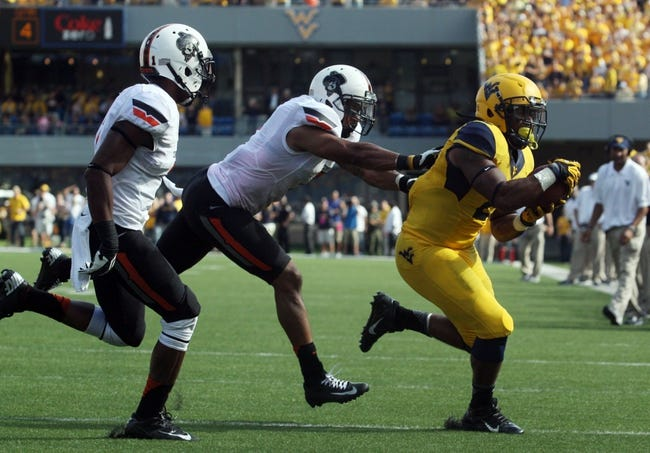 Sep 28, 2013; Morgantown, WV, USA; West Virginia Mountaineers running back Dreamius Smith (2) is pushes out of bounds by Oklahoma State Cowboys safety Shamiel Gary (7) before scoring a touchdown during the second half at Milan Puskar Stadium. Mandatory Credit: Peter Casey-USA TODAY Sports