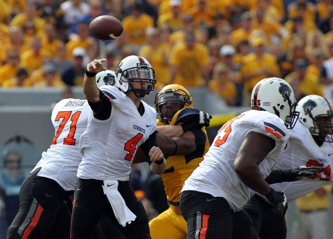Sep 28, 2013; Morgantown, WV, USA; Oklahoma State Cowboys quarterback J.W. Walsh (4) passes the ball against the West Virginia Mountaineers at Milan Puskar Stadium. Mandatory Credit: Peter Casey-USA TODAY Sports