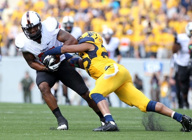 Sep 28, 2013; Morgantown, WV, USA; Oklahoma State Cowboys wide receiver Tracy Moore (87) is tackled by West Virginia Mountaineers safety Darwin Cook (25) during the second half at Milan Puskar Stadium. Mandatory Credit: Peter Casey-USA TODAY Sports