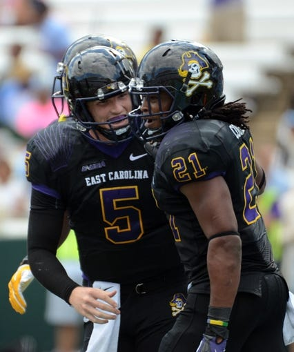 Sep 28, 2013; Chapel Hill, NC, USA; East Carolina Pirates quarterback Shane Carden (5) and running back Vontavious Cooper (21) celebrate a third quarter touchdown against the North Carolina Tarheels at Kenan Memorial Stadium.  ECU won 55-31. Mandatory Credit: Rob Kinnan-USA TODAY Sports