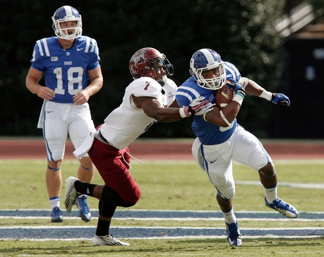 Sep 28, 2013; Durham, NC, USA;  Troy Trojans safety Chris Pickett (7) defends as Duke Blue Devils running back Josh Snead (9) runs the ball at Wallace Wade Stadium. Mandatory Credit: Mark Dolejs-USA TODAY Sports