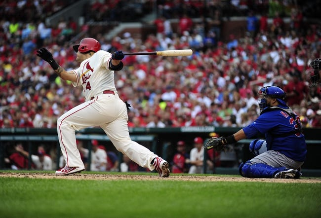 Sep 28, 2013; St. Louis, MO, USA; St. Louis Cardinals catcher Yadier Molina (4) hits a two run double off of Chicago Cubs starting pitcher Edwin Jackson (not pictured) during the third inning at Busch Stadium. Mandatory Credit: Jeff Curry-USA TODAY Sports