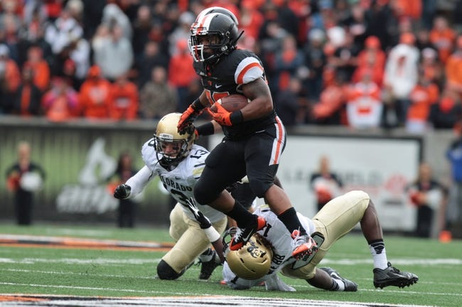 Sep 28, 2013; Corvallis, OR, USA; Oregon State Beavers running back Terron Ward (28) runs the ball as Colorado Buffaloes linebacker Derrick Webb (1) reaches for his legs at Reser Stadium. Mandatory Credit: Scott Olmos-USA TODAY Sports