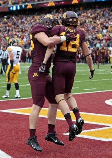 Sep 28, 2013; Minneapolis, MN, USA; Minnesota Golden Gophers wide receiver Derrick Engel (18) celebrates with tight end Maxx Williams (88) after scoring a touchdown in the second half against the Iowa Hawkeyes at TCF Bank Stadium. The Hawkeyes won 23-7. Mandatory Credit: Jesse Johnson-USA TODAY Sports