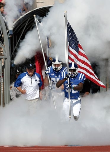 Sep 28, 2013; Durham, NC, USA;  Duke Blue Devils head coach David Cutcliffe runs out onto the field with tight end Dan Beilinson (85) and wide receiver Brandon Watkins (30) before the start of their game against the Troy Trojans  at Wallace Wade Stadium. Mandatory Credit: Mark Dolejs-USA TODAY Sports