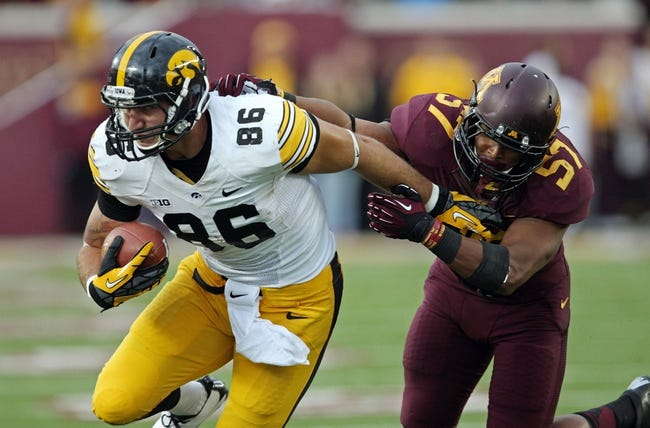 Sep 28, 2013; Minneapolis, MN, USA; Iowa Hawkeyes tight end C.J. Fiedorowicz (86) attempts to break away from a tackle by Minnesota Golden Gophers linebacker Aaron Hill (57) in the second half at TCF Bank Stadium. The Hawkeyes won 23-7. Mandatory Credit: Jesse Johnson-USA TODAY Sports