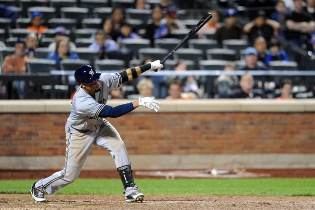 Sep 28, 2013; New York, NY, USA; Milwaukee Brewers center fielder Carlos Gomez (27) hits an RBI single in the tenth inning against the New York Mets at Citi Field. Mandatory Credit- Joe Camporeale-USA TODAY Sports
