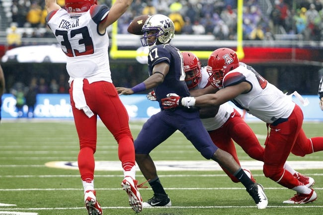 Sep 28, 2013; Seattle, WA, USA; Washington Huskies quarterback Keith Price (17) throws a touchdown pass while under pressure from Arizona Wildcats linebacker Marquis Flowers (2) and defensive lineman Reggie Gilbert (84, right) during the first quarter at Husky Stadium. Mandatory Credit: Joe Nicholson-USA TODAY Sports