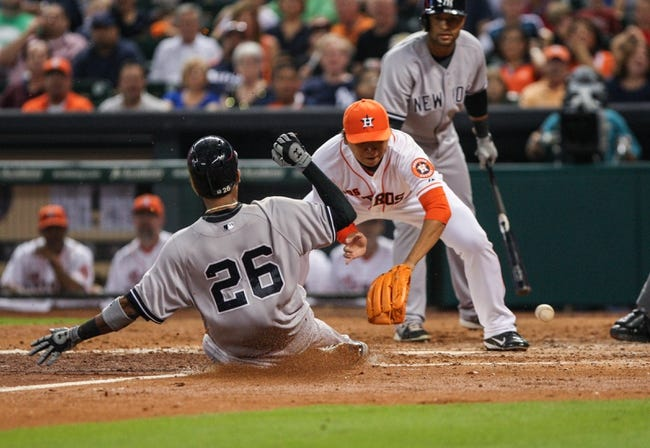 Sep 28, 2013; Houston, TX, USA; New York Yankees shortstop Eduardo Nunez (26) slides safely into home plate during the sixth inning as Houston Astros relief pitcher Chia-Jen Lo (63) attempts to apply a tag at Minute Maid Park. Mandatory Credit: Troy Taormina-USA TODAY Sports