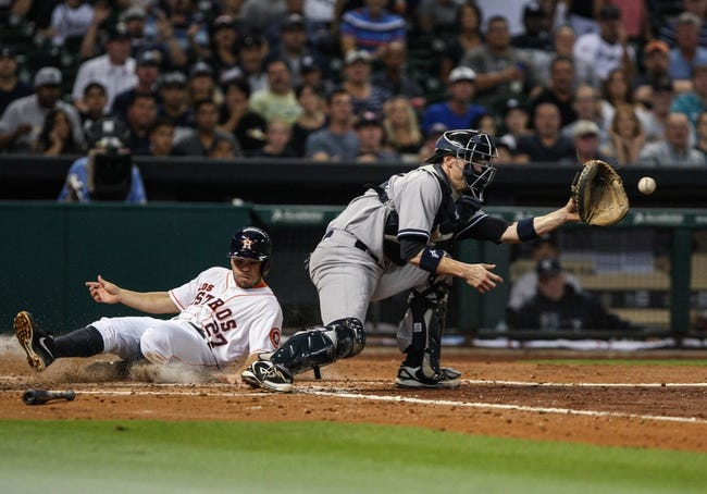 Sep 28, 2013; Houston, TX, USA; Houston Astros second baseman Jose Altuve (27) scores a run during the fourth inning as New York Yankees catcher Chris Stewart (19) attempts to field the throw at Minute Maid Park. Mandatory Credit: Troy Taormina-USA TODAY Sports