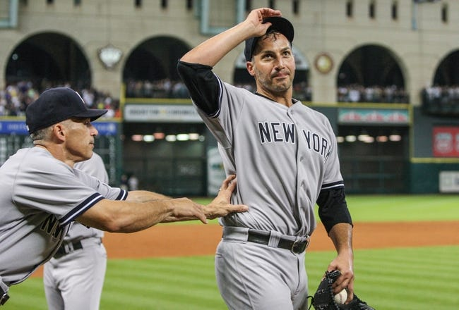 Sep 28, 2013; Houston, TX, USA; New York Yankees manager Joe Girardi (28) pushes starting pitcher Andy Pettitte (46) back onto the field after defeating the Houston Astros 2-1at Minute Maid Park. Mandatory Credit: Troy Taormina-USA TODAY Sports